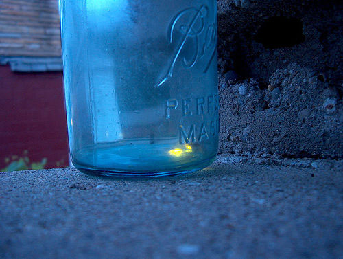 Glowing firefly trapped in Mason jar